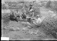 Sitting figures of three workers, excavations head G. D. Belov, and excavation architect S. F. Strzheletskiy